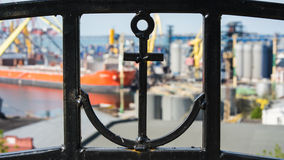 A fence with an anchor and a sea port. In the foreground can be seen an anchor in an iron fence. Back blurred the background you can see sea trade port and the Royalty Free Stock Image