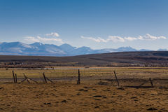 Fence on the background of the high snowy mountains Stock Photos