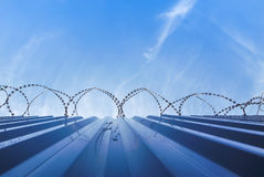 Fence with barb wire and blue sky Royalty Free Stock Photos