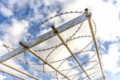 Fence With Barb Wire. Barb Wire Fence With Blue Sky And Clouds Stock Photos