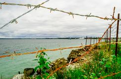 Fence of Barb wire protect coastline of sea royalty free stock photos