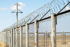 Fence with barbed wire. (small depth of sharpness Royalty Free Stock Images