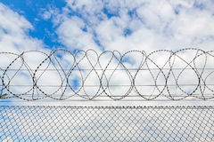 Fence with barbed wire. Against blue sky with clouds Stock Photos