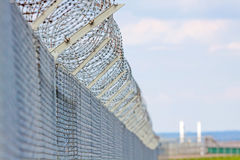 Fence with barbed wire. Against blue sky with clouds Stock Images