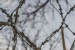 Fence with barbed wire against the sky stock photography