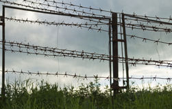 A fence with barbed wire. On the background of the grey sky Stock Photos