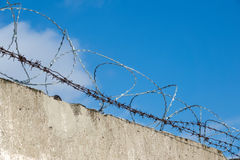 Fence with barbed wire. Blue sky. Clouds. Royalty Free Stock Photo