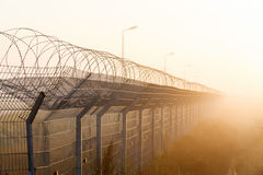 Fence with barbed wire on the border. Of the object at dawn with fog in the summer, russia Royalty Free Stock Photo