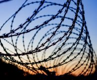 Fence with a barbed wire. Under a blue sky Royalty Free Stock Image