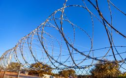 Fence with a barbed wire. Under a blue sky Stock Images