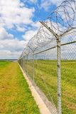 Fence with barbed wire. Green landscape and blue sky with clouds Royalty Free Stock Photo