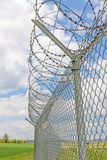 Fence with barbed wire. Green landscape and blue sky with clouds Stock Photos