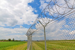 Fence with barbed wire. Green landscape and blue sky with clouds Stock Images