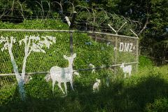 Fence with barbed wire in green nature, trees and bushes with painted deer on the fence along the DMZ, the third tunnel Royalty Free Stock Photography