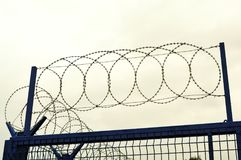 Fence with barbed wire. Fence with barbed wire on a guarded private territory Royalty Free Stock Photography
