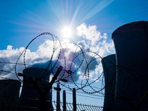 Fence with Barbed Wire. Power Plant behind Fence with Barbed Wire Stock Photography