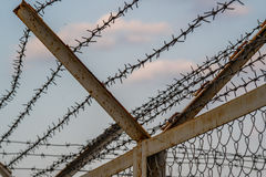 A fence with barbed wire. Are prohibited to enter the restricted area Royalty Free Stock Photo