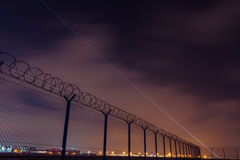 Fence with barbed wire, restricted area and starting plane.  Stock Image