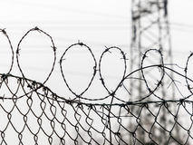Fence with barbed wire. A fence is secured with barbed wire. symbolic photo for security, prison and crime Royalty Free Stock Photo