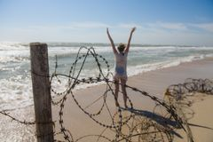Fence with barbed wire and silhouette of woman stock photos