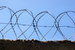 Fence with barbed wire. On the sky background Stock Image