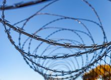 Fence with a barbed wire. Under a blue sky Stock Photography