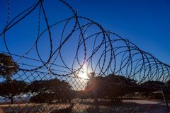 Fence with a barbed wire. Under a blue sky Stock Image