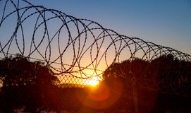 Fence with a barbed wire. Under a blue sky Royalty Free Stock Photos
