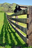 Fence and barn. On the hilly meadow Royalty Free Stock Image