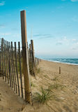 Fence on a beach. A wooden fence with a patch of grass by the shore Stock Images