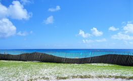 Fence by the beach. Beautiful blue ocean and the blue sky Stock Photo