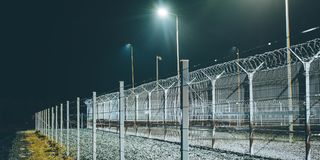 Fence boarder security. Night lights barrier zone area Royalty Free Stock Images