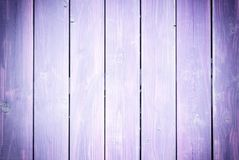 Fence of boards painted in violet. Background with the texture of wooden slats. Photo with a vignette royalty free stock image