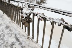 The fence of the bridge with the symbols of a strong marriage union, closed locks. Winter. Old rusty locks symbolize the strength of marriage in Russia. They royalty free stock image