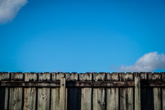 Fence. A background of blue sky and a wood fence Royalty Free Stock Images