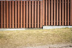 Fence of brown wooden boards. Wooden fence with dry grass under it stock images