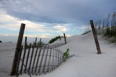 Fence buried in sand dunes and pretty skies. Sand dunes are protected by fences for bird habitat Royalty Free Stock Image