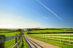 Fence casting shadows on a road leading to small house between scenic Cornish fields under blue sky, Cornwall, England Stock Image