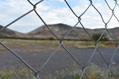 Fence in a city border. With mountains ahead Stock Photography