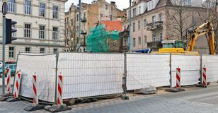 The fence closes the construction site of the reconstruction of the old city street. Panoramic collage from several urban shots royalty free stock photos