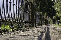 Fence and cobbles in the park. In Lisbon, Portugal. The summer sun casting the fence`s shadow on the cobbled path stock photography