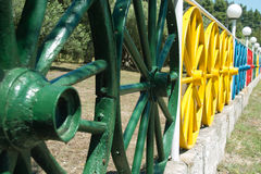 Fence color. Fences made of wooden wheels carts painted in various vibrant colors Stock Image