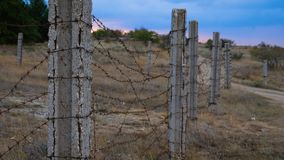 The fence of concrete pillars and rusty barbed wire. stock video