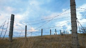 The fence of concrete pillars and rusty barbed wire. stock video footage