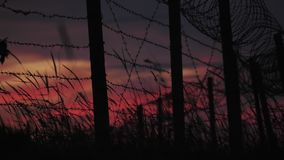 The fence with barbed wire and grass on the background of a cloudy red-blue sky. stock video footage