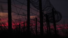 The fence with barbed wire and grass on the background of a cloudy red-blue sky. stock video