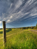 Fence in the countryside. A barbed-wire fence running along the road out in the country Stock Photos