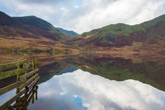Fence in Crummock Water lake. Early morning on the shore of Crummock Water a lake situated in the area called The Lake District in Cumbria,UK.            The royalty free stock image