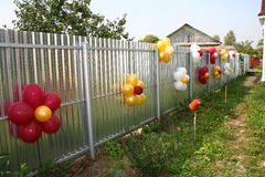 The fence is decorated with balloons Stock Images