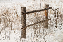 Fence at a  dirt road's edge  surrounded by dry bushes Royalty Free Stock Image